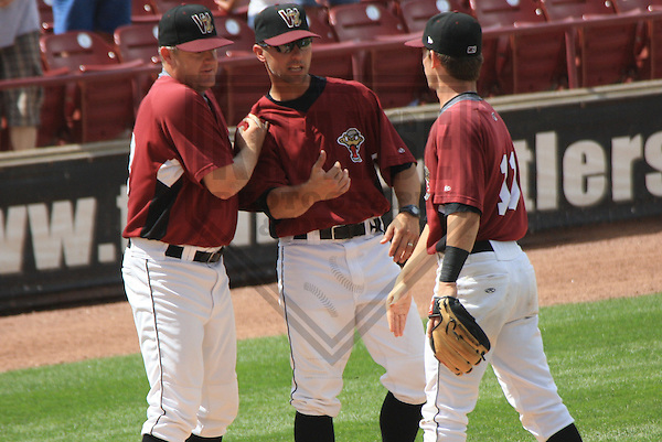 APPLETON - JULY 2010: Jeff Isom (33), Matt Erickson (24) and Scooter Gennett (11) of the Wisconsin Timber Rattlers, Class-A affiliate of the Milwaukee Brewers, celebrate a victory after a game on July 12, 2010 at Fox Cities Stadium in Appleton, Wisconsin. (Photo by Brad Krause)