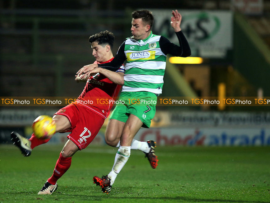 George B Williams of MK Dons clears the ball upfield under pressure from Yeovil's Kevin Dawson during Yeovil Town vs MK Dons, Checkatrade Trophy Football at Huish Park on 6th December 2016