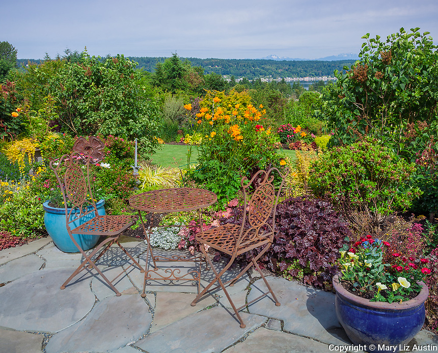 Vashon-Maury Island, WA: Iron table and chairs on flagstone patio with a view of a terraced garden and of Quartermaster Harbor