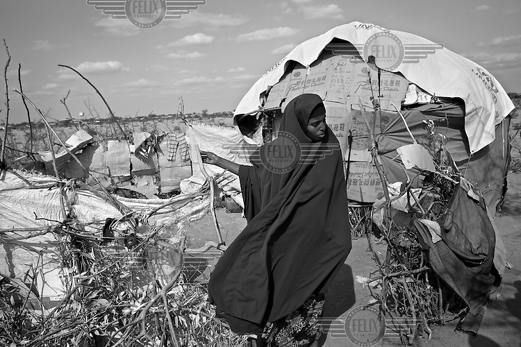 A woman stands outside her makeshift home. Thousands of families in desperate need of food and water have trekked for days from Somalia to the Dadaab refugee camp. The drought is the worst in East Africa for 60 years. The UN described it as a humanitarian emergency. The already overcrowded complex received 1,000 new refugees a day in June, five times more than a year ago. About 30,000 people arrived at the Dadaab refugee camp in June, according to UNHCR compared to 6,000 in June 2010.