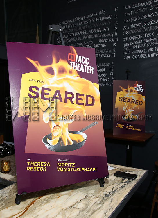 "Poster signage during the photo call for the cast and creative team of MCC Theater's New York Premiere of ""Seared"" on September 11, 2019 at Artesia Wine Bar in New York City."