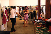 May 26, 2009. Durham, NC..Nadira Hurley, owner of Vert & Vogue, assists JoAnn, Herb and Emily Amey browse the store's collection of clothing made only of organic material at reasonable prices.