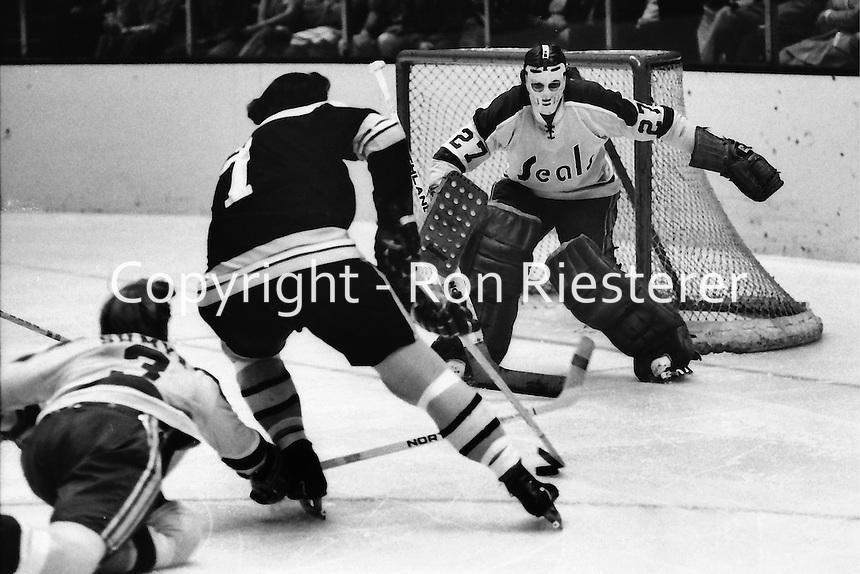 Boston Bruin Phil Esposito rush on Seal goalie Gilles Meloche. (1972 photo/Ron Riesterer)