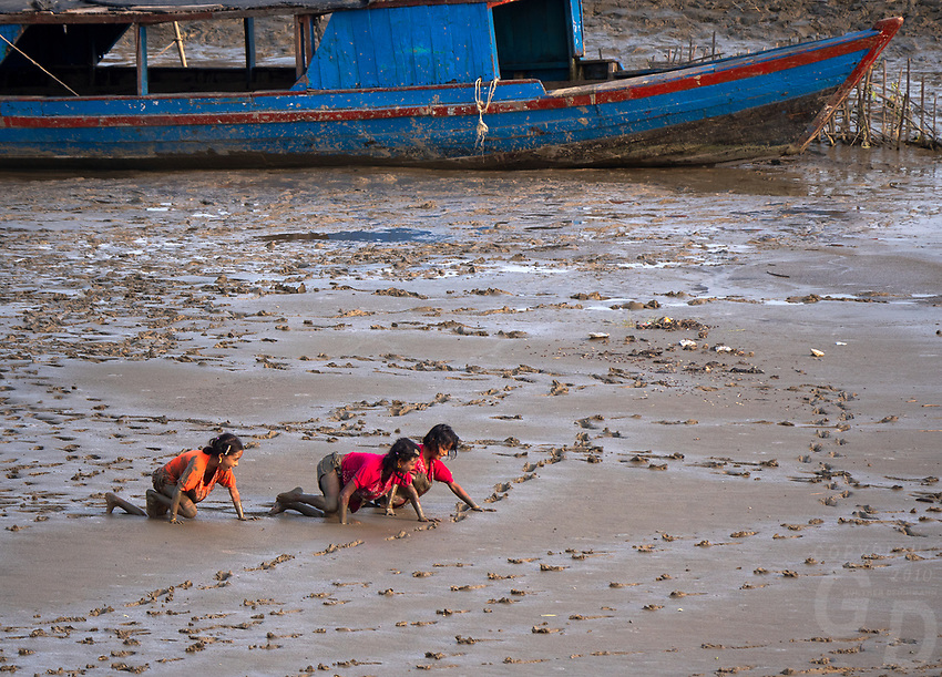 Children playing and crawling in the mud at a river bank flood plains, Rakhine State, Myanmar