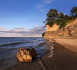 A Boulder Sitting In The Surf With Cliffs Behind Radiating Morning Light, Lake Erie At Barcelona Beach, New York, USA
