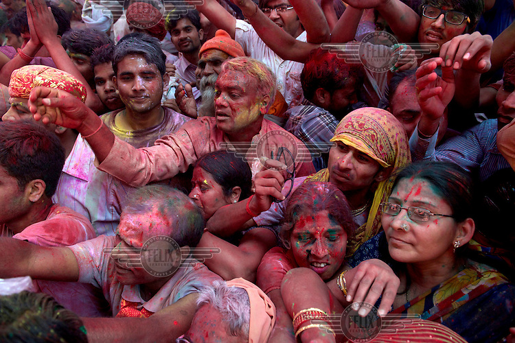 Revellers smeared with coloured powder, gather at the Shriji Temple (Laadli Sarkar Mahal) during Lathmar Holi. The festival is held during a full moon and the town fills with tourists and revellers making the pilgrimage for a glimpse of 'God', the Lord Shiva, who is revealed inside the temple only fleetingly.