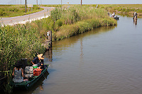 Several boats of people enjoying weekend fishing along one of the canals running through Sabine National Wildlife Refuge, Louisiana.  Editorial use only.