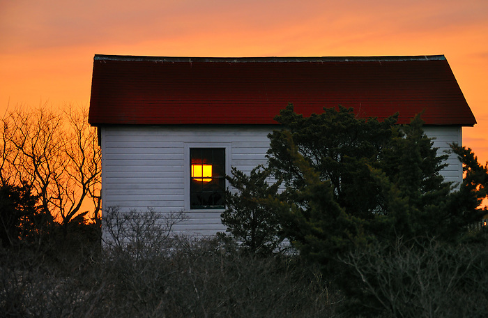 A fiery sunrise peeps through the window of an old shack by the Fire Island lighthouse