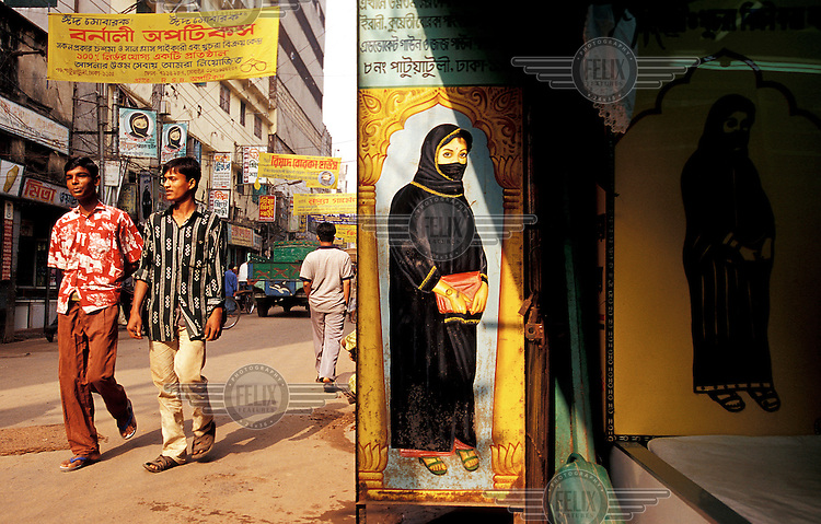 Bnagladesh; Dhaka.  Men wearing fairly western dress walk past row of shops in Old City district of Dhaka dedicated to selling traditional burqa-style clothing to women.  Credit: Chris Stowers.