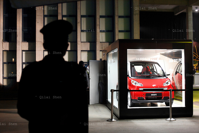 A guard stands near a smart for two vehicle on display during the smart for two China Launch in Shanghai, China on 08 April 2009. China's automobile market saw a rapid growth in the past decade and it is now the biggest automobile market in the world, the title has come with a price however, with many cities roads clogged, some local governments are issuing new directives limiting new vehicle purchases.