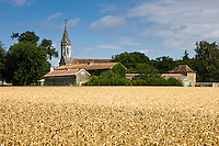 Traditional church and village scene across wheat field at Mondion, Loire Valley, France