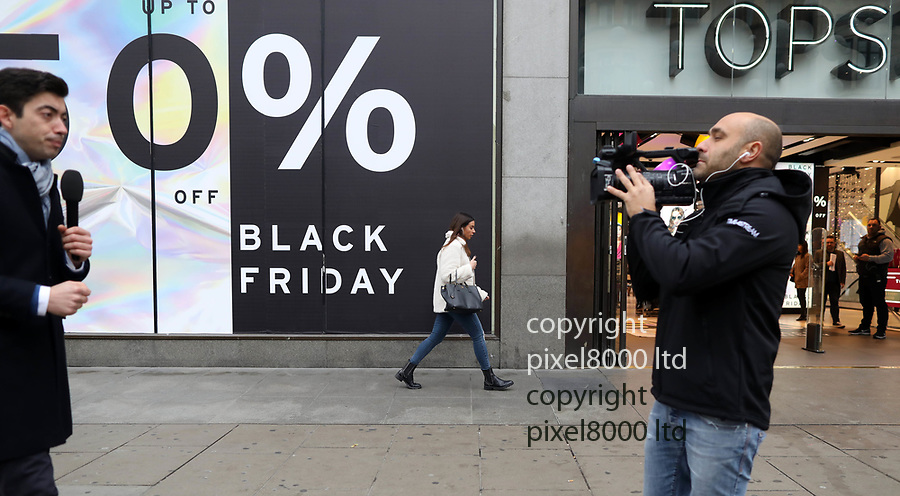 Pic shows: Black Friday sales<br /> <br /> Italian TV crew filming the sales as<br /> <br /> <br /> Shoppers were largely underwhelmed today around Oxford Street but there were large queues outside Apple Shop before it opened.<br /> Apple store did not have official sale but were giving cash back on certain items<br /> <br /> <br /> <br /> <br /> pic by Gavin Rodgers/Pixel8000