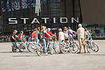 Group of cyclists outside central railway station building, Centraal Station, Rotterdam, Netherlands