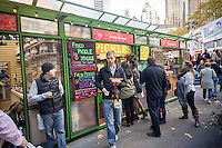 Scores of visitors to the Bryant Park Holiday Market line up at the Pickle Me Pete kiosk to satiate themselves on orders of fried pickles, seen on Saturday, November 19, 2016.  (© Richard B. Levine)