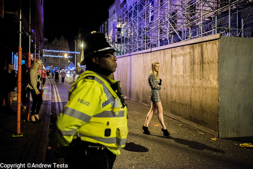 UK. Northampton. 7th December 2013<br /> A policeman watches as young people make their way between bars in Northampton town centre.<br /> &copy;Andrew Testa for the New York Times