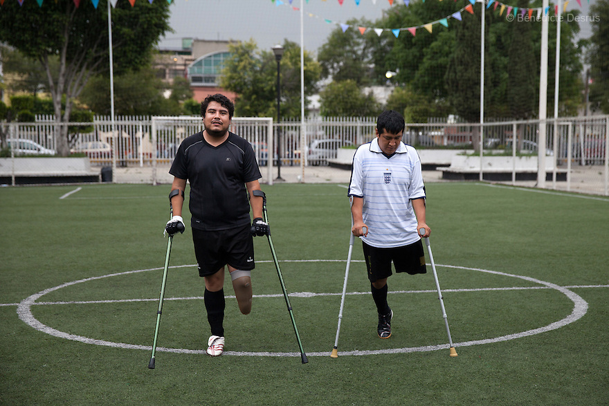 "Osman (L) and Salvador (R), both players from Guerreros Aztecas, during a training session with the team in Mexico City, Mexico on June 26, 2014. Osman Cristobal González Ruiz, 31, lost his left leg in an electrical accident at work when he was 23. Salvador Avendaño Vasquez, 25, lost his left leg in a car accident in may 2010. Guerreros Aztecas (""Aztec Warriors"") is Mexico City's first amputee football team. Founded in July 2013 by five volunteers, they now have 23 players, seven of them have made the national team's shortlist to represent Mexico at this year's Amputee Soccer World Cup in Sinaloa this December. The team trains twice a week for weekend games with other teams. No prostheses are used, so field players missing a lower extremity can only play using crutches. Those missing an upper extremity play as goalkeepers. The teams play six per side with unlimited substitutions. Each half lasts 25 minutes. The causes of the amputations range from accidents to medical interventions – none of which have stopped the Guerreros Aztecas from continuing to play. The players' age, backgrounds and professions cover the full sweep of Mexican society, and they are united by the will to keep their heads held high in a country where discrimination against the disabled remains widespread. (Photo by Bénédicte Desrus)"