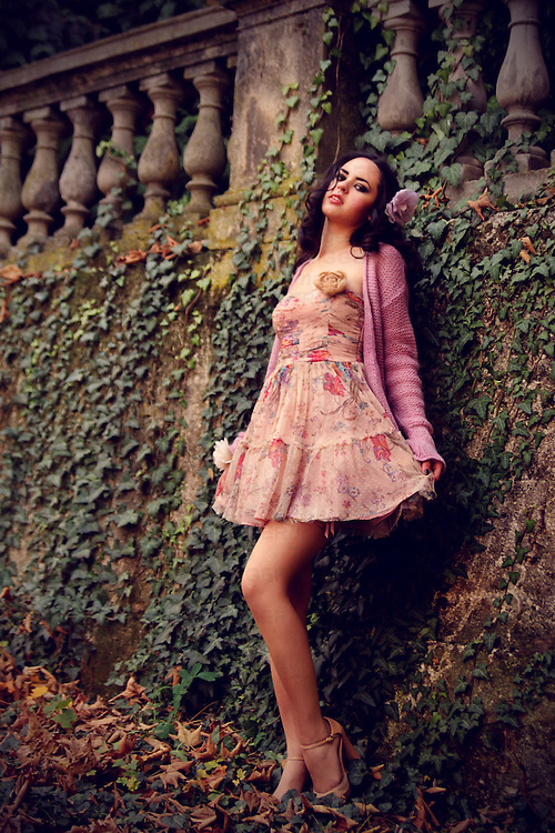 A pretty brunette in a pastel floral dress posing in a garden leaning onto a wall.