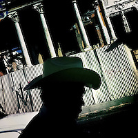 A Salvadorean man, wearing a cowboy hat, walks along a ruined colonial building on the street of San Salvador, 20 December 2013.