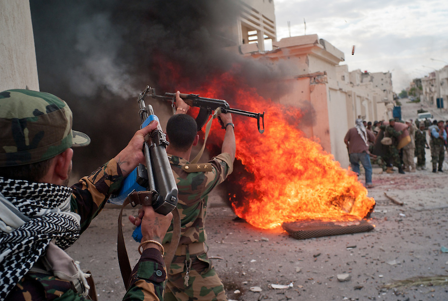 Anti-Gaddafi fighters exchange fire with Gaddafi loyalists in Sirte, Libya.