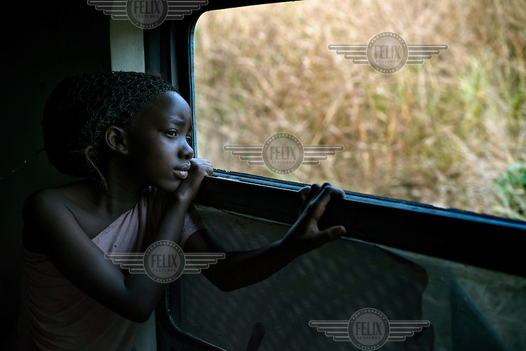 Faria, a former refugee, looks out the window of a train bound from Kinshasa to Kimpesi from where buses will take her and others to the Angolan border.<br /> She says: 'I want to become a doctor because my uncle and my aunt [in Angola] are doctors. There are many doctors in my family. This is what I heard. I have never met them.' Maria's family, along with nearly 500 other former refugees, departed Kinshasa to return to return to Angola on 19 August, 2014. The journey, made on train and bus, took approximately 36 hours to reach the Angolan border. The UNHCR is coordinating the return of nearly 30,000 former refugees to Angola.