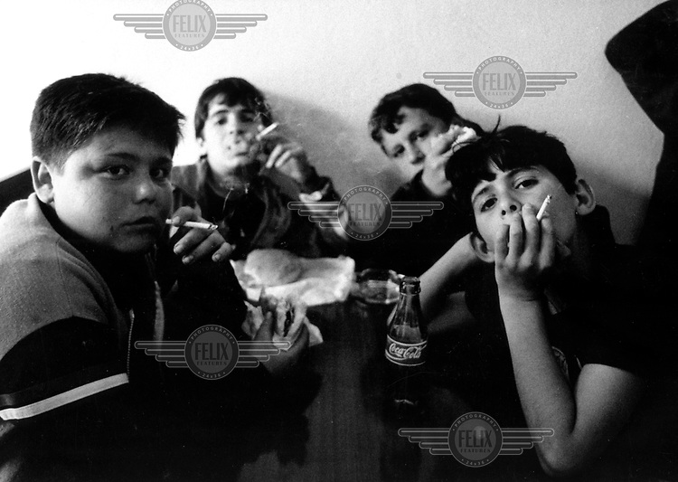 ©Melanie Friend/Panos Pictures..Albania. 13 year old boys smoking and drinking Coca Cola in a cafe in Berat.