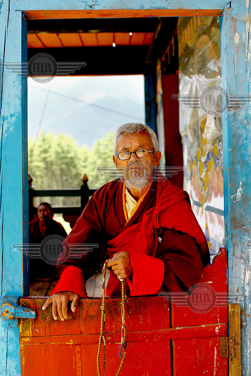 An elderly monk holds prayer beads at the Taktsang (Dzong) Monastery high up in the Paro Valley.