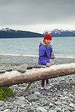 USA, Alaska, Homer, a young girl lines up rocks on an old log at Land's End beach, the Homer Spit