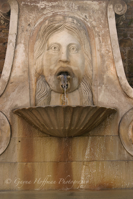 Ancient fountain with face and water pouring out of it's mouth, Rome, Italy