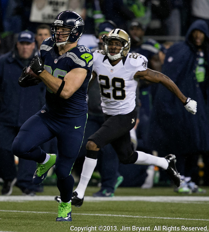 Seattle Seahawks tight end Zach Miller (86) runs away from New Orleans Saints cornerback Keenan Lewis (28) and runs for a first down during the first quarter at CenturyLink Field in Seattle, Washington on December 2, 2013. The Seahawks lead the Saints 27-7 at the half.  ©2013. Jim Bryant Photo. ALL RIGHTS RESERVED.