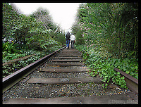 two people walking along abandoned railroad tracks bordering Lk. Union, Seattle