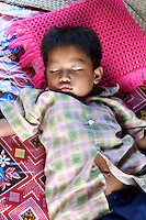 Sleeping child in floating village house on Tonle Sap Lake in Cambodia
