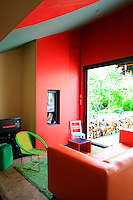 The living area is picked out in bright lego colours and a sliding window opens directly onto the terrace beyond