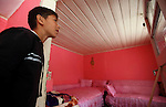 Roma families in Barbulesti, Romania. Duduveica family share   a house in Barbulesti together with 3 other families since they have been deported from France. A boy is showing the room where Duduveica family, a 4 persons family, uses for sleep.