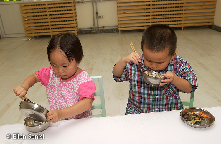 Beijing, China.Little Oak Children's House: private day care center and private elementary school..Girl and boy use chopsticks to eat meat, vegetables, and rice at lunchtime..© Ellen B. Senisi