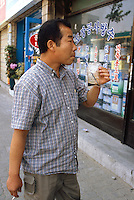 Korea. South Korea. Incheon. 30 km from Seoul. A man drinks dog juice with a straw in the street. Pressing shops sells to customers ( men and women)  juice from  dogs pressed. It is supposed to be good for the health. Dog meat is a delicatessen of korean traditionnal cooking.  © 2002 Didier Ruef