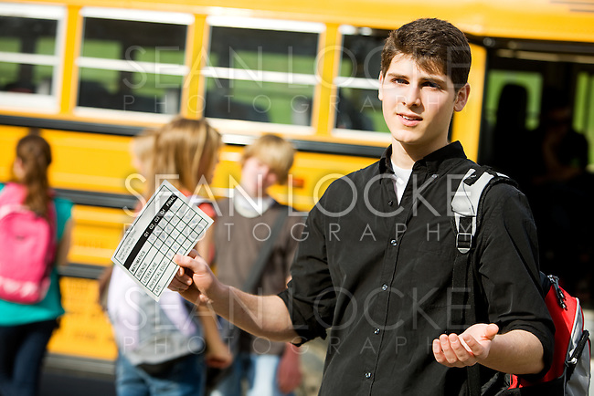 Series with multi-ethnic group of teenage students boarding and on a school bus. Holding a report card with grades.
