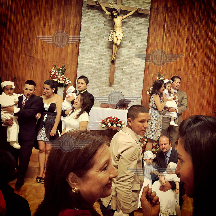 Families mingle and pose for photos after baptising their young children in the church of La Primavera, a wealthy neighbourhood of Cumbaya.