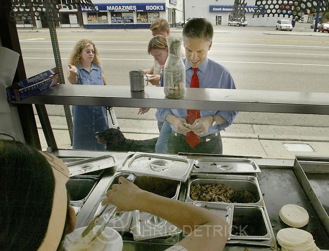 "Salt Lake City, UT--16 Jun 2005--.Utah Governor Jon Huntsman buys a taco from Marina Romero at the taco stand ""Don Rafai"" on the corner of State St. and 800 S. Thursday afternoon. ..Chris Detrick /Salt Lake Tribune"