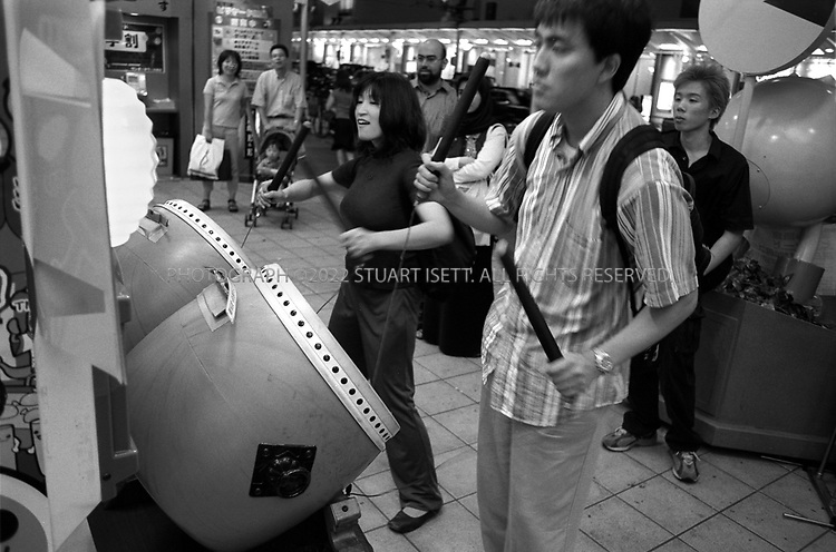 July, 2001--Kyoto, Japan..Tourists play a video game with traditional Japanese Taiko drums on Kawaramachi Street...All photographs ©2003 Stuart Isett.All rights reserved.This image may not be reproduced without expressed written permission from Stuart Isett.