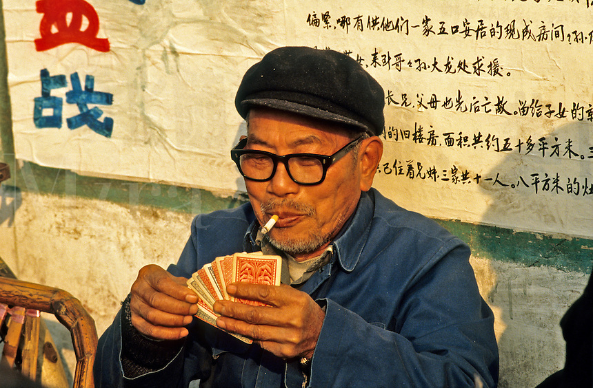 China. Man playing cards outside.
