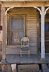 Wooden chair on front porch of old wooden house.