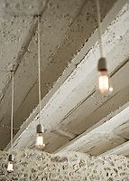 In the dining room minimally elegant pendant lights work well against the original stone walls and ceiling