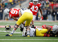 Ohio State Buckeyes defensive lineman Joey Bosa (97) tears the helmet off Michigan Wolverines quarterback Devin Gardner (98) during the 4th quarter of the NCAA football game at Ohio Stadium on Nov. 29, 2014. (Adam Cairns / The Columbus Dispatch)