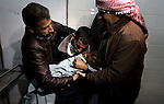 A Palestinian relative carries the lifeless body of 3-year-old Hala Abu Sebakha, who medics said was killed by shrapnel during an Israeli air strike on the Al Maghazi camp, at the morgue of Al-Aqsa hospital in Deir Al Balah, central Gaza Strip, Tuesday, Dec. 24, 2013. Israeli air and ground forces launched a series of attacks Tuesday on targets across the Gaza Strip, killing a young girl and wounding 10 in response to the deadly shooting of an Israeli civilian by a Palestinian sniper. Palestinian officials reported at least 16 Israeli attacks, causing a causing a series of loud explosions across the territory in rapid succession. Hamas ordered its forces to evacuate offices and compounds and redeploy to safer sites. Photo by Ashraf Amra