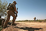 Marines from Company L, 3rd Battalion, 6th Marine Regiment sprint across a dirt road as they flank a Taliban machine gun position after being attacked near Marjah, Afghanistan. March 11, 2010. DREW BROWN/STARS AND STRIPES
