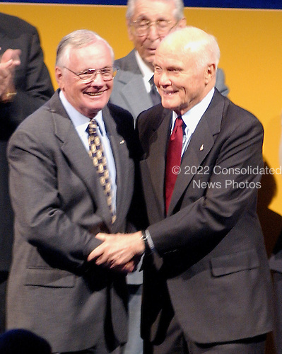 Chantilly, VA - December 11, 2003 -- Space pioneers Neil A. Armstrong and John H. Glenn share an embrace as they are introduced during the dedication of the National Air and Space Museum's Steven F. Udvar-Hazy Center in Chantilly, Virginia on December 11, 2003.  Armstrong flew the X-15 rocket plane, was the mission commander for Gemini 8, and on July 20, 1969, as commander of the Apollo 11 mission, ws the first human to walk on the Moon.  Glenn became the first American to orbit the Earth on February 20, 1962.  Subsequently, he served as a United States senator from Ohio and was a mission specialist on the space shuttle STS-95 mission in October, 1998..Credit: Ron Sachs / CNP.(RESTRICTION: NO New York or New Jersey Newspapers or newspapers within a 75 mile radius of New York City).