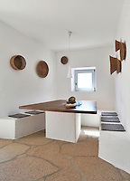 The minimal dining area is furnished with a wooden table top on a concrete base surrounded by a built-in banquette