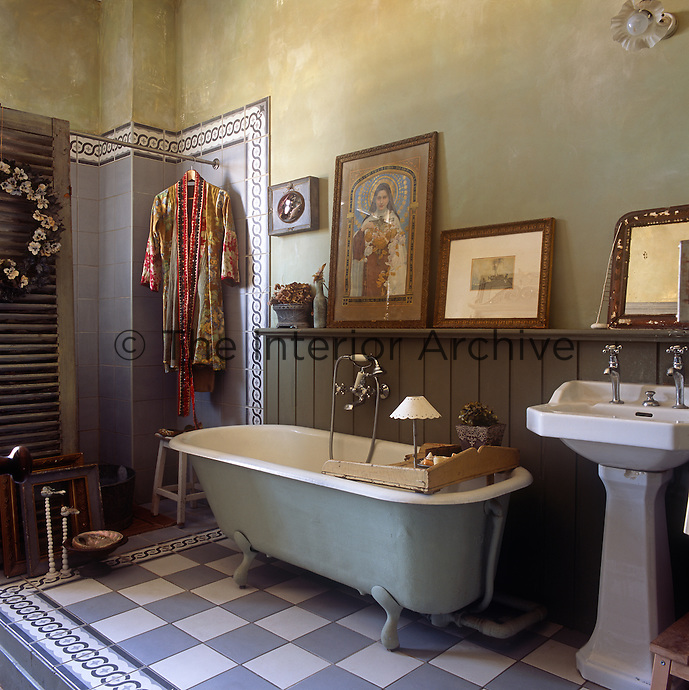 A traditional bathroom with a pedestal washbasin and a freestanding bath on a blue and white tiled floor.
