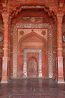 Fatehpur Sikri, Uttar Pradesh, India.  Mihrab (Niche indicating the direction of Mecca) and Prayer Hall of the Jama Masjid (Dargah Mosque).  Hindu-style arch framing Islamic arch over the mihrab.