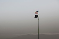 A U.S. flag  and a POW-MIA flag against a muted background with the outline of the Santa Cruz Mountians and afternoon fog rolling over them and into San Francisco Bay.